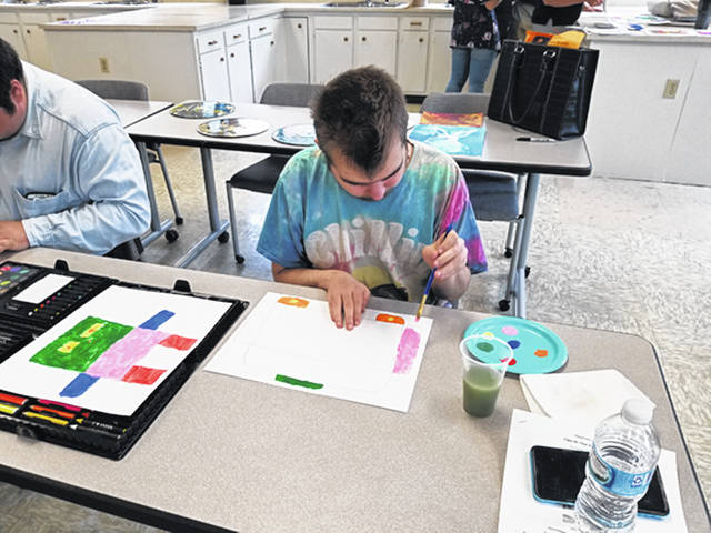 Bethany J. Royer-DeLong | Darke County Media Jacob Parsons focuses on his artwork at Memorial Hall on Thursday. Parsons was one of a dozen differently-abled artists set to work on projects for entry at the Fine Arts Show at the upcoming 163rd Great Darke County Fair.