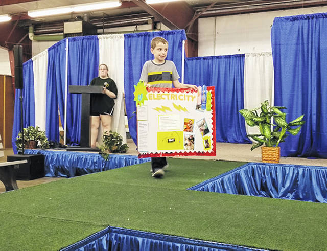 Bethany J. Royer-DeLong | Darke County Media Daniel Williams, 9, of the Blue Angels 4-H Club, presented his project on an open and closed circuit during the STEM revue held at the youth building during the 163rd Great Darke County Fair on Saturday.