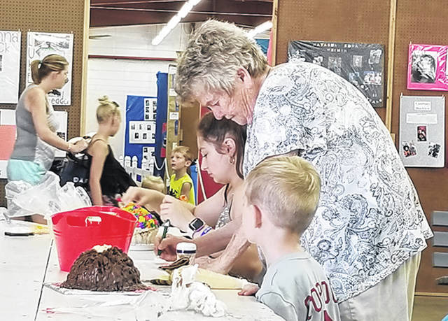Bethany J. Royer-DeLong | Darke County Media The two contestants for the cake decorating contest were Brittany Thobe, 15, of Versailles, and Braxton Martin, 6, of Greenville, pictured with Louann Jess, judge, at the 163rd Great Darke County Fair on Monday.