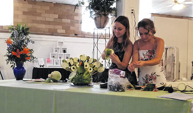 "Bethany J. Royer-DeLong | Darke County Media Sisters Olivia Wysong-Kauffman and Eliza Wysong, Butterflies Junior Garden Club members past and present, created an ""edible animal"" during the Darke County Association of Garden Clubs' Garden Highlights held during the 163rd Great Darke County Fair on Sunday."