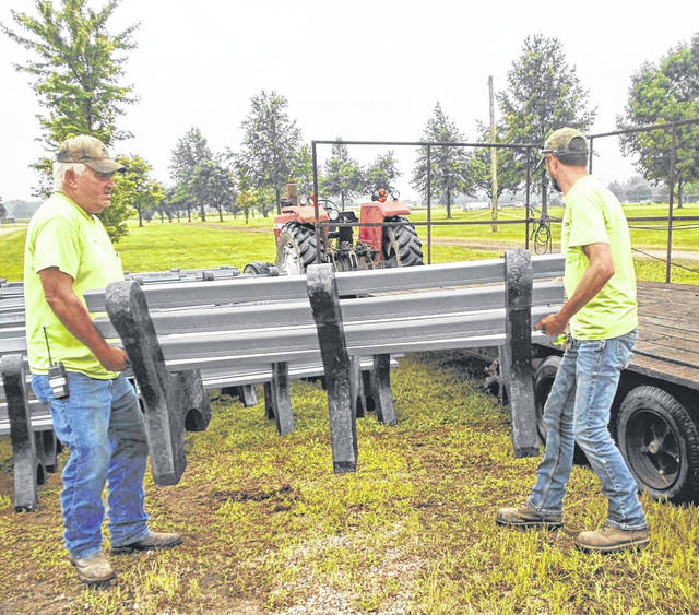 Darke County Fair caretakers Jerry Byerly, left, and John Strawser start loading up the benches, made of recyclable bottle caps and lids, to distribute them around the fairgrounds for the upcoming festival.