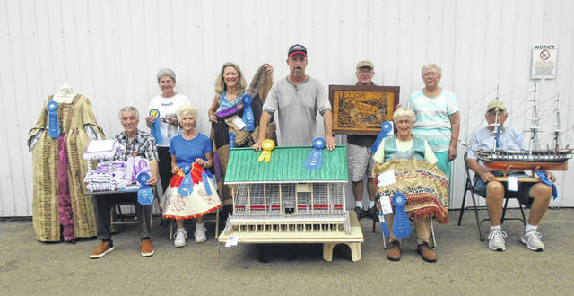 Kenny Coates Jr., center, stands beside the Grandstand he created and made him a rosette winner and best of show in the Domestic Arts Department during the fair. Also shown are rosette winners, seated from left to right, Tim Nealeigh, Anna Mae Johnson, Laura Hinders and Ken Pence; and standing, Sarah Jane Sewell, Barb Hodson Jerry Manning and Barb Lavy.