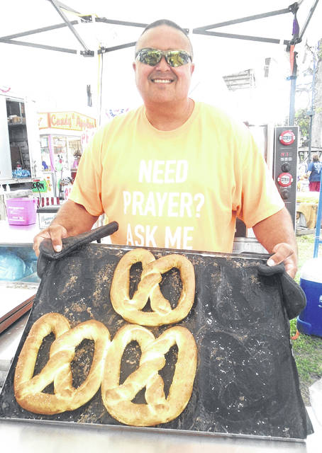 Allen Zifer holds up a tray of Heavenly Pretzels he made for a Darke County Fair customer. The Zifers are from Florida, but have worked in this area all summer. The stand was here last year at a different location.