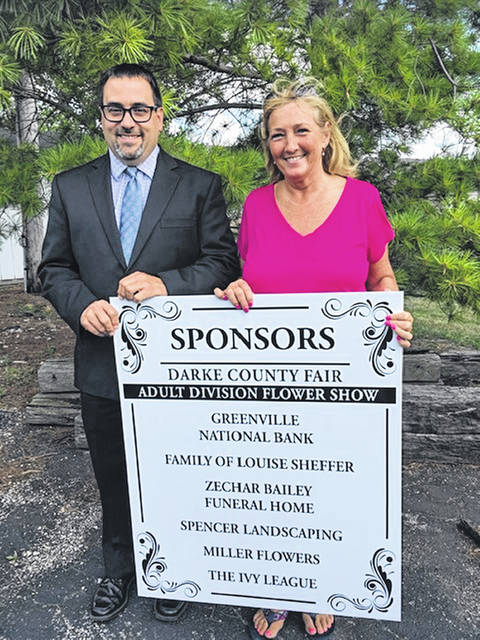 Greg Zechar of Zechar Bailey Funeral Home and Darke County Fair Flower Show Director Kim Cromwell hold a sign thanking sponsors of the yearly event.