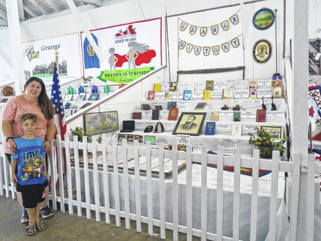 Susan Gunckle, shown with nephew Calen Clopp, stands at the new historical booth for Stelvideo Grange this year at the Great Darke County Fair. It's located in the Domestic Arts building.