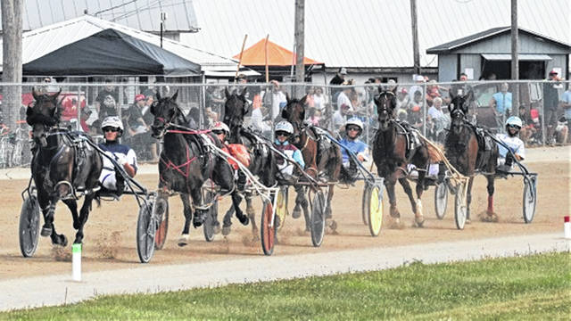 Race horses come down the stretch towards the finish line at the Great Darke County Fair.