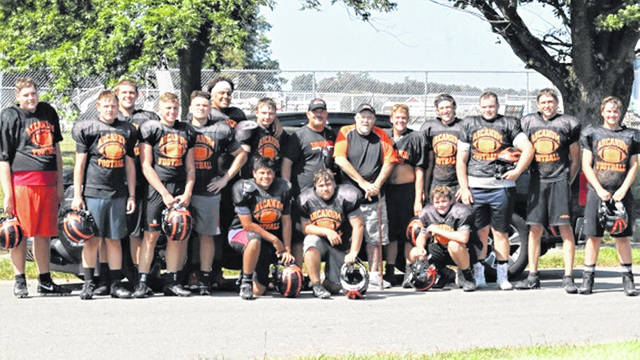 Coach Schondelmyer (center L) and Coach Greg Hale (center R) share a moment with the Arcanum High School offensive and defensive lines at the team's football practice.