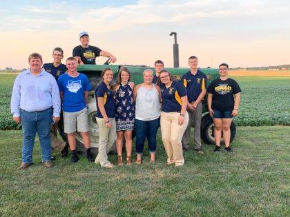 Versailles FFA members that assisted with the Farm Mass on the tractor seat Caleb Smith, left to right: Caden Buschur, Nicholas Didier, Wesley Gehret, Deanna Hesson, Renea Schmirmeyer, Shelbie Schmitmeyer, Laura Wuebker, Luke Billenstein, Noah Barga and Emily Delzeith.