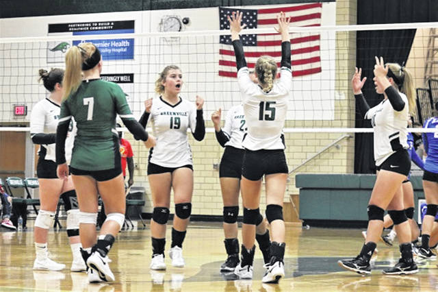 The Lady Wave varsity volleyball team celebrates a point in the team's 3-0 win over the visiting Xenia Lady Buccaneers.