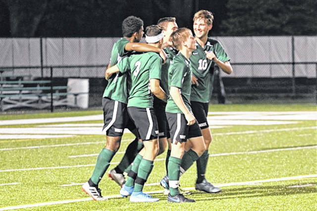 Kaleb Poe (No. 10) is congratulated by his Green Wave teammates for his goal to give Greenville a 3-0 lead over the Stebbins Indians soccer team.