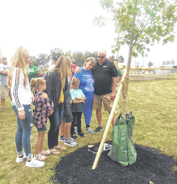 Ray Lutz's widow and children as well as his mother, who holds on to Joe Marker, check out the tree and plaque now located in Sater Heights Ballpark. Lutz loved baseball and Greenville, as well as his family.