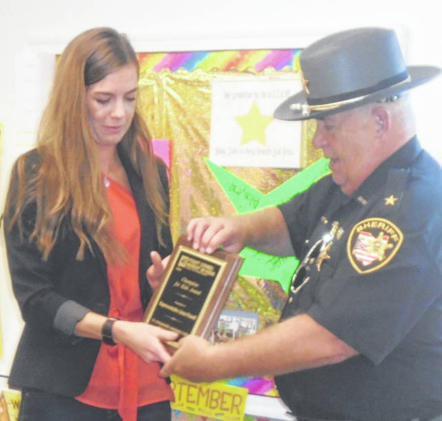 Darke County Sheriff Toby Spencer presents a plaque to Rep. Jena Powell after the two of them read to the Head Start children at Kids Learning Place on Friday. She was honored to receive the Fight Crime: Invest in Kids Ohio Champion for Children Award.