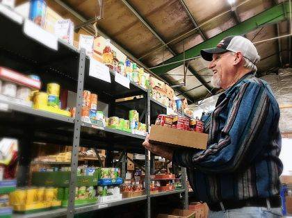 A Fish Choice Pantry volunteer is shown stocking the shelves.