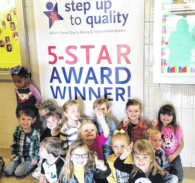 A class of 3-5 year-olds pose in front of the banner designating Anthony Wayne Early Learning Center as a 5-Star Step Up to Quality school.