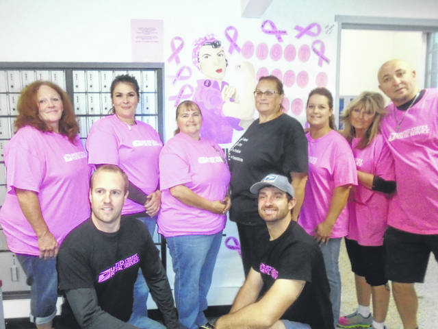 """Last Friday, employees at the Greenville Post Office showed their support of Breast Cancer Awareness Month by wearing pink U.S. Postal Service shirts to work. Here, they pose in front of their sign indicating that support. Shown are, kneeling, rom left to right, Matt Evans and Tyler Parks; and standing, Marilyn Petty, Faye Valdez, Tina Myers, Diana Valdes, Amy Pearson, RoxAnne Riegle and Scott Robinson. """"Most of us have a family member battling it,"""" said Supervisor Tabitha Fourman. The sign inside the post office reads: 'Greenville Post Office stands with you in fight.' """"Customers seem to like it,"""" Fourman said. Valdes and Robinson are clerks; Parks is a city carrier; and the rest of rural carriers."""