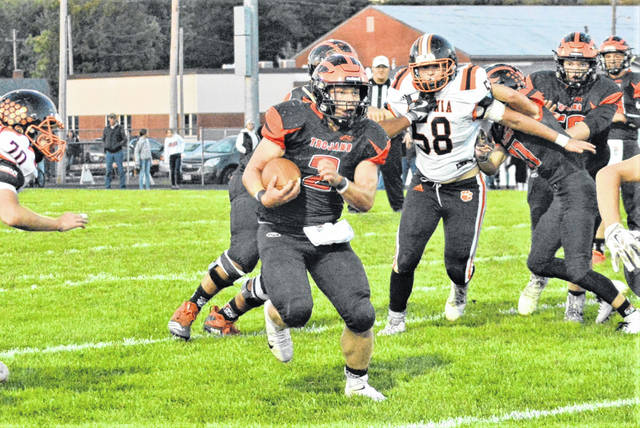 Cory Ross carries the ball for the Arcanum Trojans in the team's homecoming win over the Ansonia Tigers.