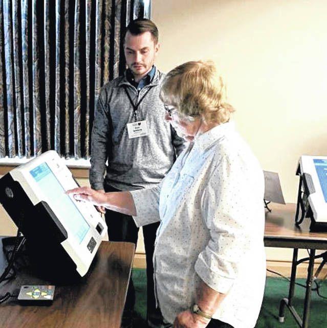 Shirley Hughes practices using one of the new Ballot Marking Device with Darke County Board of Elections Director Paul Schlecty at the recent board of elections open house.