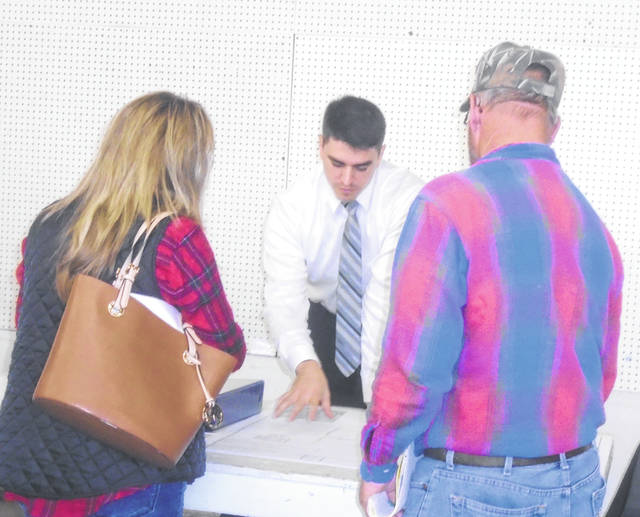 Sam Mullins, behind the table, talks with a couple of the attendees at the public hearing Tuesday night. Mullins is chief of the Division of Livestock Permitting at the Ohio Department of Agriculture.