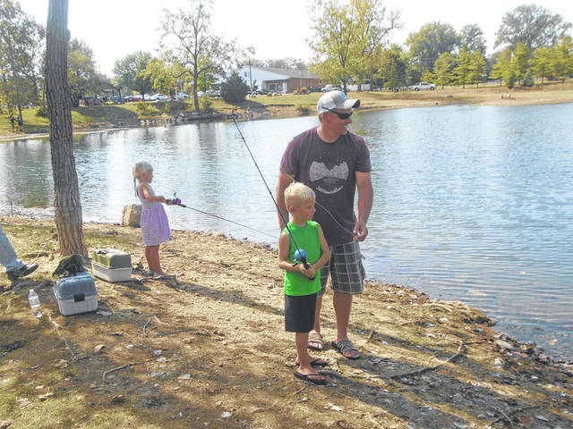 Joe Sowers assists his son, Jaxson, in fishing at Kids Fishing Day, while his daughter and Jaxson's twin sister Brinley also takes part. The twins are 5 years old.