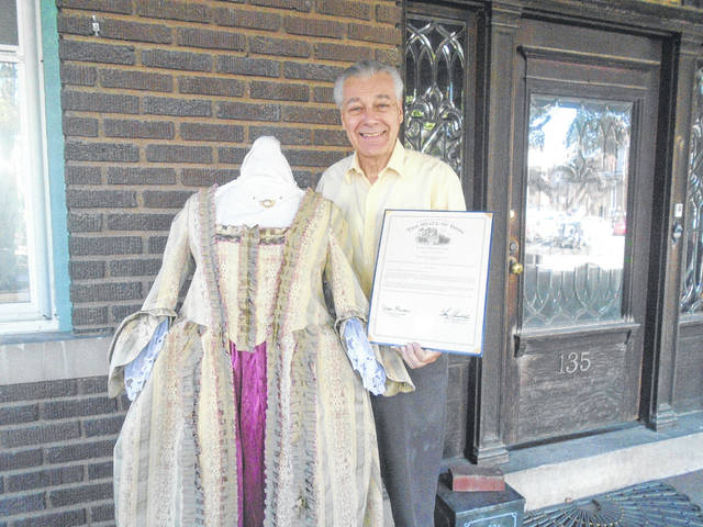 Tim Nealeigh proudly shows off the certificate he received from the Ohio House of Representatives for winning entries in this year's Great Darke County Fair, which include this historical dress.