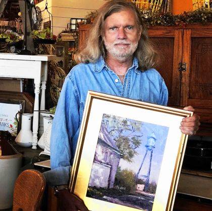 "Professional artist Patrick Kluesner of Anderson is shown with his oil painting ""The Watertower""."