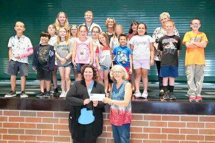 Christy Bugher, executive director of the United Way, left, joins Empowering second and fourth graders during their first day of After School Tutoring, and presents United Way's first quarterly check for 2019-20 to Greenville Program Coordinator Kay Sloat.