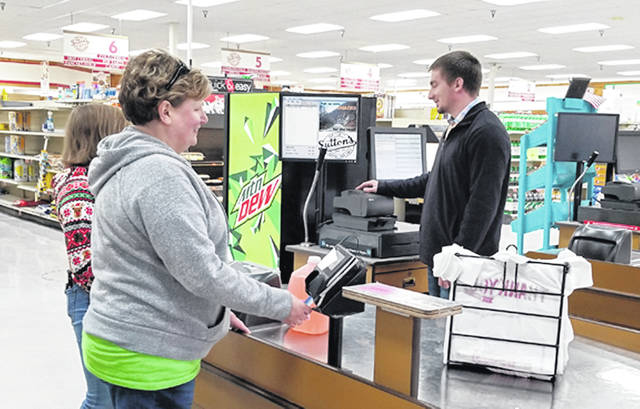 Adam Oda, Sutton's Foods employee, helps a customer with their purchases on Wednesday.