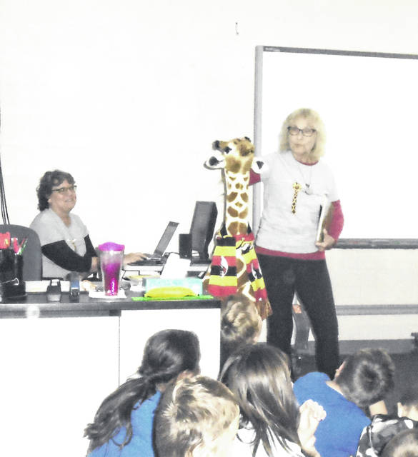 "Patty Huston-Holm, right, introduces the ""giraffe"" she and Kathy McFerrin, in background, brought to the Bradford School for their presentation about their new book."