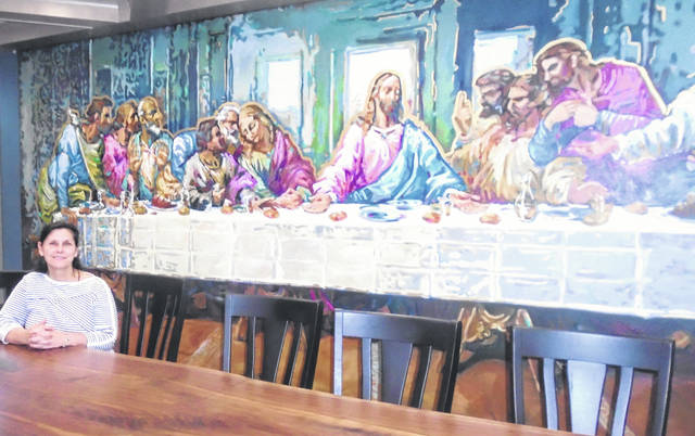 Karen Homan sits at one of the tables at the Do Good Restaurant and Ministry, which will be the scene of an open house Friday and Saturday. The Last Supper mural is a concersation piece behind her.