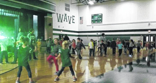 Greenville first-graders kick up their heels during their Kids Read Now dance party to music provided by DJ 911.