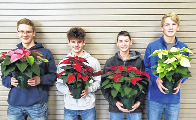 Animal and Plant Science students Mason Garber, Andrie Stephens, Colton Beatty, and Bradley Rumble display just a few of the poinsettias raised by the students in the agriculture classes at Franklin Monroe High School.