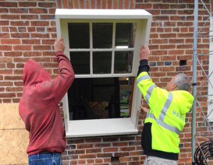 Daughters of the American Revolution get help replacing a window during their Day of Service.