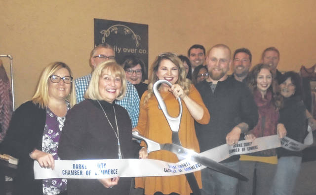 Darke County Chamber of Commerce President Sharon Deschambeau and other affiliates assisted with the grand relocation open house and ribbon-cutting at Happily Ever Co., located at 303 S. Broadway. Owner Sarah Schinke Hall holds the scissors. Also in attendance were the Hall's family members and friends.