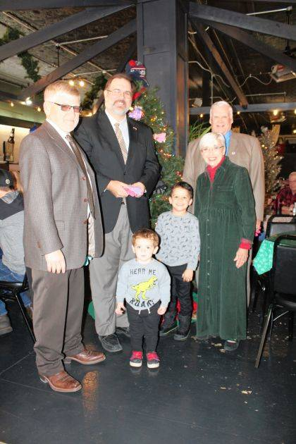 Darke County Commissioners Mike Rhoades, Matt Aultman and Mike Stegall are joined by Lincoln, 2, and Maddox, 4, and Mitten Tree coordinator Marilyn Delk. Lincoln and Maddox are enrolled in the Head Start program.