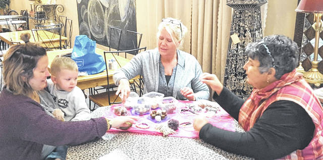 "Jackie Jones (left), owner of ""Sweets to Eat"" with her son; Kat McNew (center), owner of ""Lorelei and Noami"" discuss their products with Quarter Auction Chairlady Delores Ely. They both brought a samples to promote their businesses."