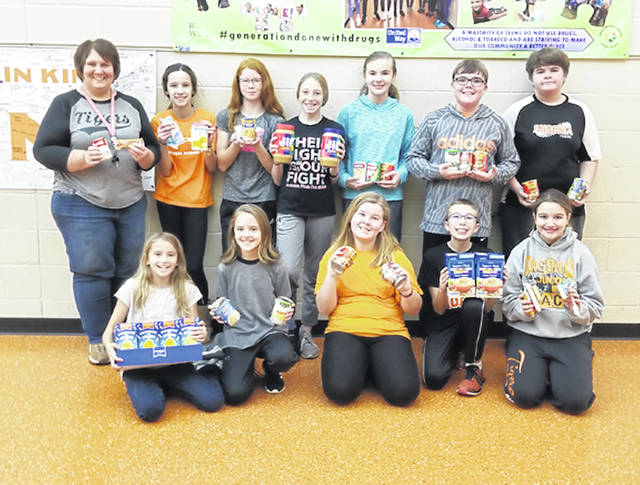 A few members of the School Safety Patrol, along with their adviser, Leslie Rhoades, showcase some of the 1,645 food items collected by the school during their annual food drive for the Ansonia United Methodist Food Bank on Friday.