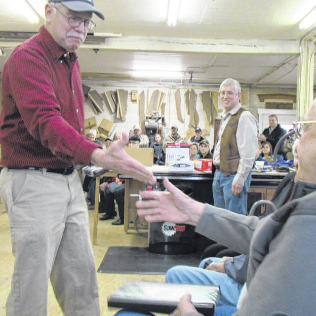 Scott Phillips, left, presents a small gift to Harry Niswonger, who celebrated his 95th birthday the day of the Wooden Toy Contest at the Ansonia Lumber. Co. Niswonger also subsequently won the competition with his tanker track.