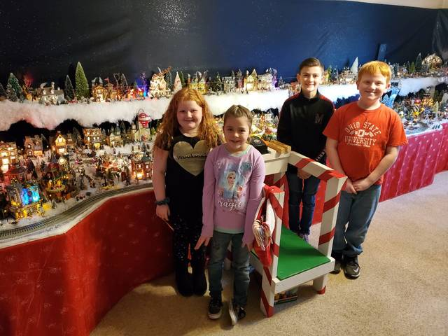 Tony and Becky Schultz's grandchildren are shown with a portion of the Christmas village set up in Tony and Becky's home west of Greenville<strong>.</strong> The grandchildren are, from left to right, Chelsea Duncan, 7 1/2, Brynlee McKee, 7, and Gauge Mckee, and Evan Duncan, both 11.