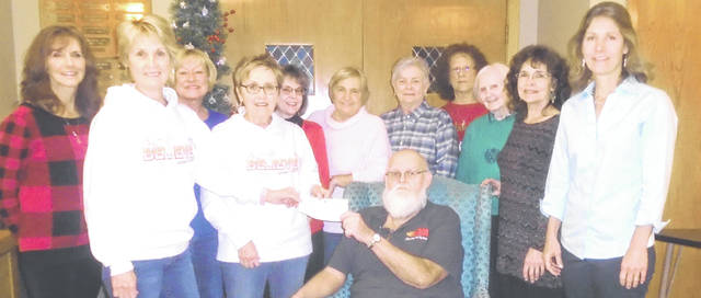 Connie Harshbarger and Becky Shumaker, second and fourth from the left in white jackets, present the Team Addiegirl contribution of $2,575 check to Duane Edwards. Looking on are, from left to right, CADC represenatives Susan Fowble, Peggy Black, Sherry Marten, Barb Fee, Sharon Kerns, Trudy Eastland, Kay Curry and Christine Lynn as well as Christy Prakel, director of the Darke County Foundation.