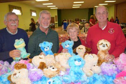 Arcanum Lions Club volunteers show off some of the stuffed animals that will soon find new homes.
