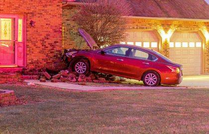 The driver of this Nissan Altima lost control and came to rest after crashing into a house.
