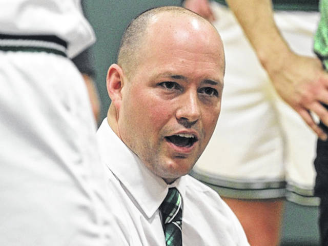 Green Wave varsity boys basketball coach Kyle Joseph encourages his player during a timeout in game with Troy.