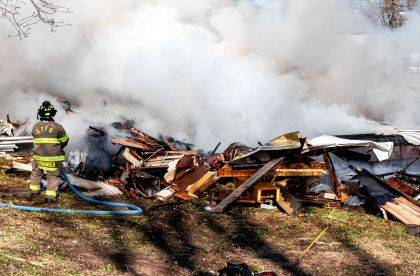 A Liberty Township Firefighter worked to put out a fire on a house trailer being razed.