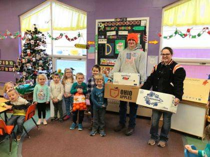 Isaac Grilliot and Kaia Kruckeburg are shown with students from Kinder Corner as the Versailles FFA recently donated a case of apples, oranges and pears to Kinder Corner.