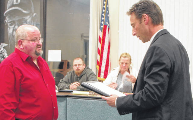 Ansonia Village Solicitor Travis Flienham, right, delivers the oath of office to Mayor Ted Adkins at the beginning of the village council meeting Tuesday night. Adkins served on council for nine years.