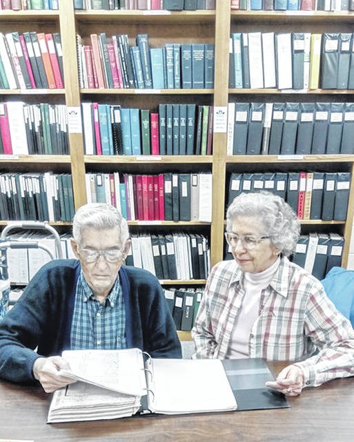 Roger McEowen and Phyllis Krick, head of genealogy at Garst Museum, look over one of the 27 notebooks and binderws he donated to the museum this week.