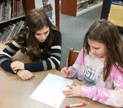 An Ansonia Big Buddy Mentor, Madison, is shown working with her Little Buddy, Grace on writing a letter to Klaus. A result of this letter writing was each students received a special gift delivered to their home.