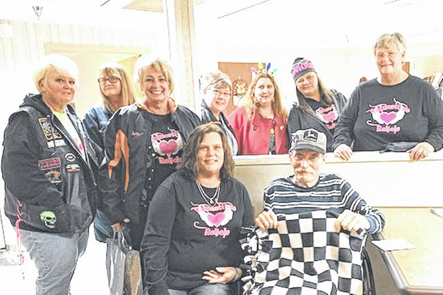 Members of the Rhinestone Rebels — Gena Hoyt, Ann Horn, Sue and Kristy Larson, Stephanie Portemont, Angela Gibbons, T.J. Rammel, Carla Lynn Hill Clark, Michelle Plessinger, Rhonda Rexrode, Angela Bright, Sherry Kniesly, Paula Adams and Diana Hileman — present one of their blankets to a veteran at one of the local nursing homes.