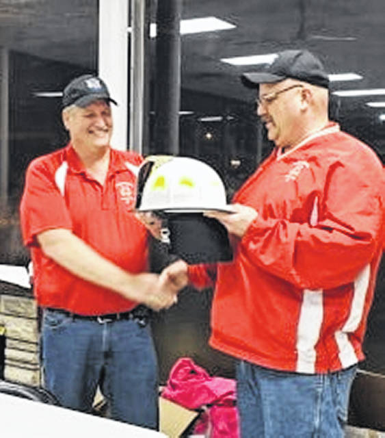 Doug Cothran, who is retiring as Rossburg Fire Department's fire chief after 20 years, turns over his helmet to Rob Widener, his successor, at the department's annual appreciation banquet Saturday night.