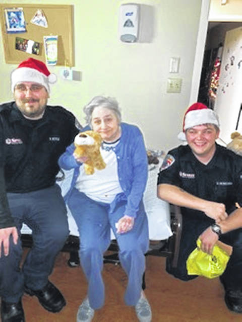 EMT Daniel Hittle, left, of Greenville and EMT Ralph Griesdorn of Mendon are all smiles as is this Van Wert nursing home resident after giving her a stuffed animal as a surprise Christmas morning.